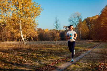 Runner training and exercising in autumn park. Woman running at sunset. Active healthy lifestyle. Workout
