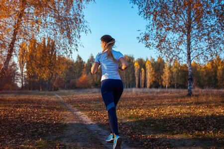 Runner training in autumn park. Woman running with water bottle at sunset. Active lifestyle. Workout