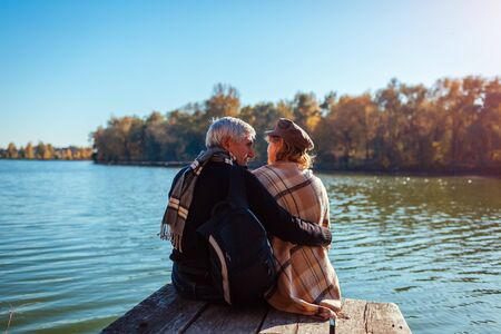 Senior family couple relaxing by autumn river. Happy man and woman enjoying natural landscape and hugging sitting on pier Stockfoto