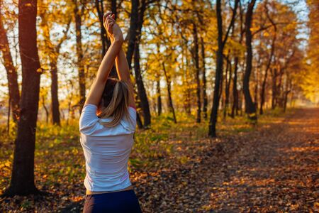 Training and exercising in autumn park. Woman stretching arms outdoors. Active healthy lifestyle. Workout