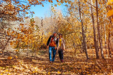 Fall activities. Senior family couple walking in autumn park. Elderly man and woman hugging and chilling outdoors.