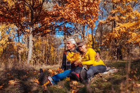 Autumn season fun. Senior couple hugging sitting in park. Happy man and woman relaxing outdoors enjoying nature