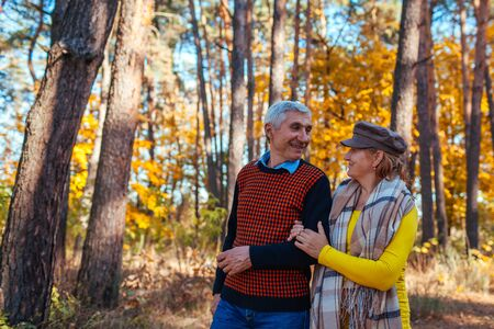 Autumn walk. Senior couple walking in fall park admiring nature. Happy man and woman talking and relaxing outdoors