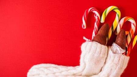 Christmas traditional sweets on red background. Colorful candy canes with chocolate Santa Clauses put in knitted socks. Flat lay, copy space. Banner
