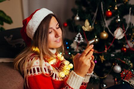 Woman hanging in Internet for Christmas using smartphone. Girl celebrating New year alone at home wearing Santas hat. Social network Stockfoto