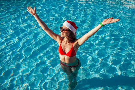 New Year and Christmas holiday. Woman in Santas hat and bikini relaxing in swimming pool, raising arms feeling happy. Tropical winter vacation Stockfoto