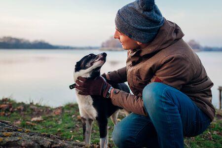 Man walking dog in autumn park by lake. Happy pet having fun outdoors. Guy talking to dog