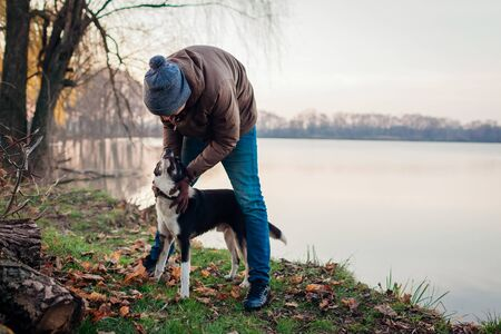 Man playing with dog in autumn park by lake. Happy pet having fun walking outdoors. Fall season activities Stockfoto