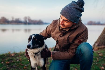 Man playing with dog in autumn park by lake. Happy pet having fun outdoors. Guy hugging dog