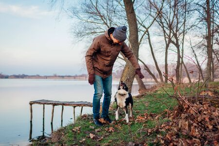 Man playing with dog in autumn park by lake. Happy pet having fun jumping and running outdoors Stockfoto
