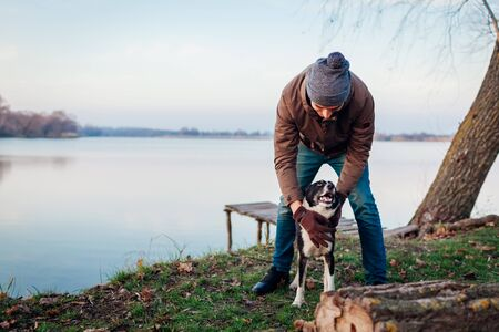 Man playing with dog in autumn park by lake. Happy pet having fun walking outdoors. Guy hugging dog. Fall activities