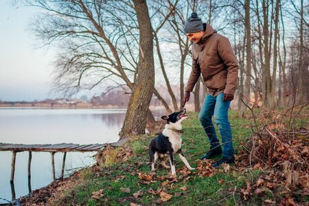 Man playing with dog in autumn park by lake. Happy pet having fun outdoors running and jumping Stockfoto