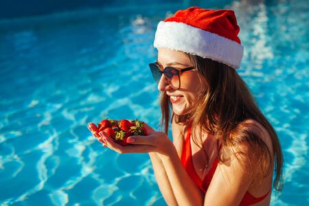 New Year and Christmas holiday. Woman in Santas hat and bikini eating strawberries fruits in swimming pool. Tropical winter vacation Stockfoto