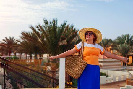 Senior woman walking on hotel territory in Egypt, Sharm-el-Sheikh. Summer tropical vacation. Stylish fashionable look