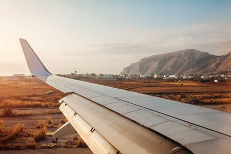 Plane landing in Fira, Santorini island. View of airplane wing. Traveling and vacation concept