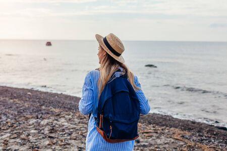 Woman traveler walking on Vlychada beach in Akrotiri on Santorini island, Greece. Tourist admiring Aegean Sea landscape