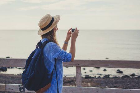 Woman traveler walking on Vlychada beach in Akrotiri on Santorini island, Greece. Tourist admiring Aegean Sea landscape and taking photo on phone