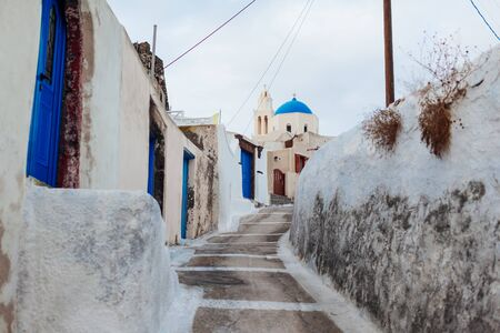 Typical street in Akrotiri village on Santorini island, Greece. White houses with blue doors. Agia Throdosia church. Traditional architecture