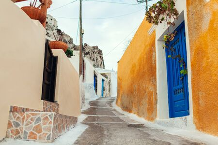 Old street in Akrotiri village on Santorini island, Greece. View of ancient castle and blue doors. Traditional greek architecture.
