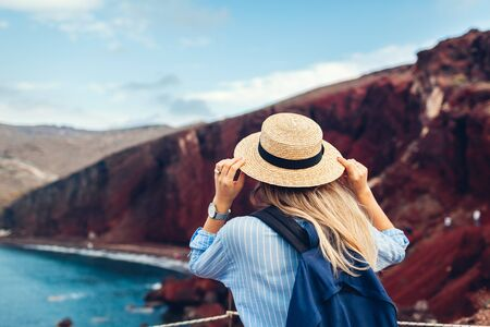 Tourist looking at Red beach landscape from view point in Akrotiri, Santorini island, Greece. Woman traveling the world