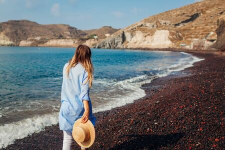 Tourist walking on coastline of Red beach in Akrotiri, Santorini island, Greece. Woman admiring seaside and mountain landscape. Traveling and vacation concept