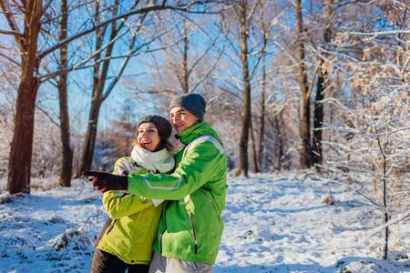 Winter seasonal activities. Happy couple in love walking and hugging in winter forest. Young people pointing and looking at something Banco de Imagens