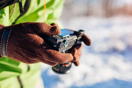 Man setting up camera. Photographer takes pictures of winter forest landscape. Close up