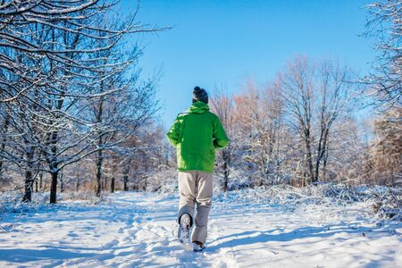 Running athlete man sprinting in winter forest. Training outside in cold snowy weather. Active healthy lifestyle. Sport Stockfoto