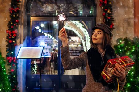 Christmas, New Year concept. Woman burning sparkler on city street by decorations. Stylish girl holding gift box present under snow. Zdjęcie Seryjne