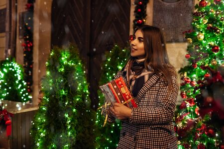 Christmas, New Year concept. Woman waiting for friends on city street by decorated cafes holding gift box. Holiday celebration