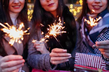 New Year concept. Women friends burning sparklers by Christmas illumination on street fair. Girls holding gift boxes celebrating holidays. Party Zdjęcie Seryjne