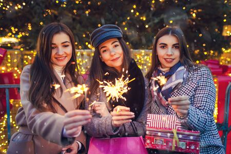 New Year concept. Women friends burning sparklers in Lviv by Christmas tree. Girls holding shopping bags and giftboxes celebrating holiday. Party