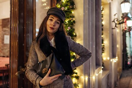 Christmas, New Year winter fashion. Woman walking on city street by decorated showcases. Stylish girl holding purse under falling snow