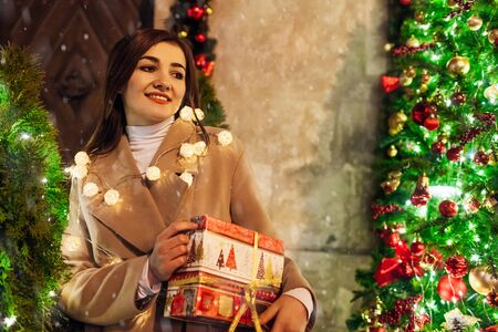 Christmas, New Year concept. Woman waiting for friends on city street by decorated tree holding gift box. Holiday celebration Zdjęcie Seryjne