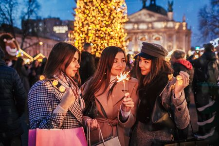 New Year eve concept. Women friends burning sparklers in Lviv by Christmas tree on street fair celebrating holidays. Happy girls holding shopping bags under snow. Party