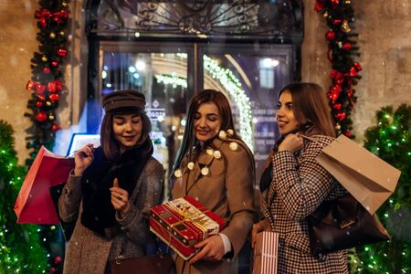 New Year, Christmas concept. Women friends holding shopping bags with presents in Lviv by decorated stores on street. Girls preparing for holidays