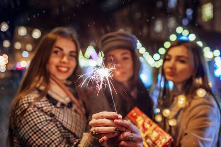New Year concept. Women friends burning sparklers in Lviv on street fair having fun with presents. Girls celebrating holidays under snow