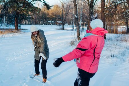 Snowballs playing in winter forest. Family mother and daughter having fun throwing snow outdoors. people relaxing during holidays