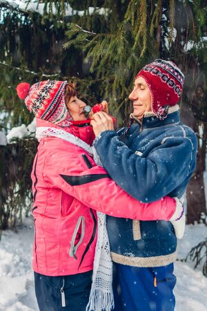 Senior couple hugging in winter forest. Man and woman walking outdoors on Valentines Day. Man tightens his wifes hat Zdjęcie Seryjne