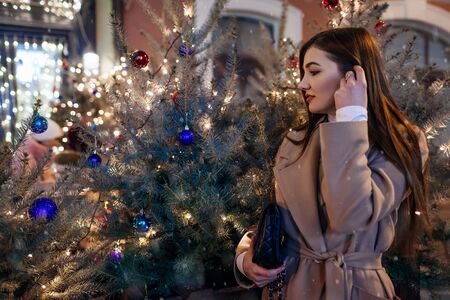 Christmas, New Year concept. Woman walking on city street by decorated trees. Stylish girl enjoying holiday magical atmosphere under falling snow