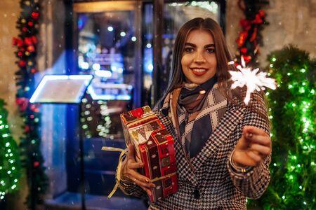 Christmas, New Year concept. Woman burning sparkler on city street by decorations. Stylish girl holding gift box present under snow. Holiday celebration Zdjęcie Seryjne