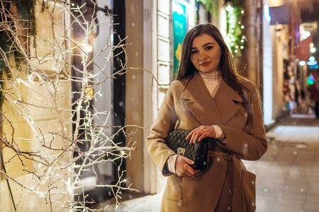 Winter holiday season. Christmas, New Year concept. Stylish woman waiting for friends by illuminated and decorated showcase on city street.