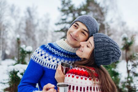 Loving couple drinking tea in winter forest. Happy people relaxing outdoors during holidays. Valentines day