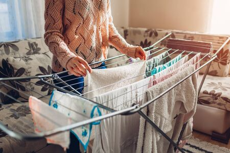 Woman hanging clean clothes on dryer after washing at home. Housekeeping and household chores