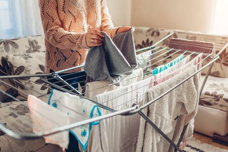 Woman folding gathering clean clothes from dryer after washing at home in living room. Housekeeping and household chores