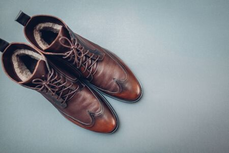 Shoes, stylish leather boots for men. Male winter, autumn or spring fashion. Brown footwear on grey background. Space. Sale