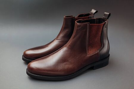 Shoes, chelsea leather boots for men. Male winter, autumn or spring fashion. Brown footwear on grey background. Sale