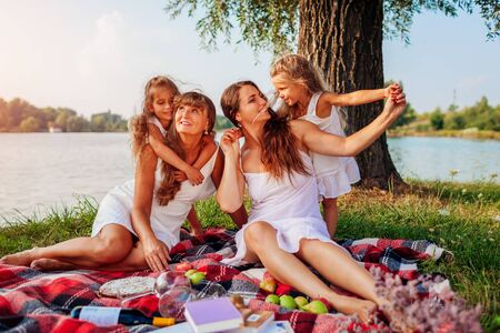 Family having picnic by summer river at sunset. Mother, grandmother and kids hugging. Three denerations spending time together. Womens day 스톡 콘텐츠