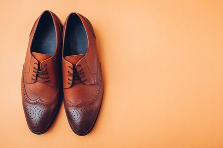 Oxford male brogues shoes. Men's fashion. Classical brown leather footwear on orange background. Top view. Space