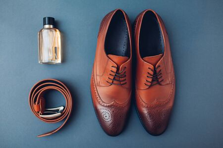 Oxford male brogues shoes with accessories. Men's fashion. Classical brown leather footwear with belt and perfume. Top view Stock Photo